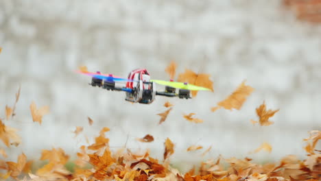 Masterly-Piloting-A-Movie-Drone-Flying-Low-Above-The-Ground-Dry-Leaves-Fly-Away-From-The-Wind-Slow-M