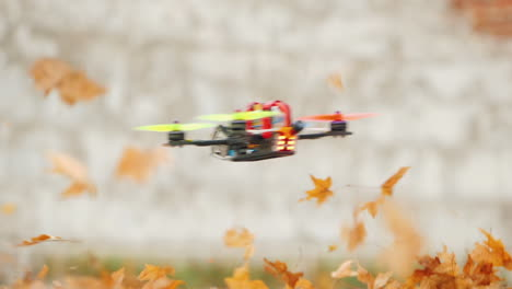 The-Drone-Flies-Quickly-And-Low-Above-The-Ground-Lifting-Leaves-From-The-Ground-In-The-Wind