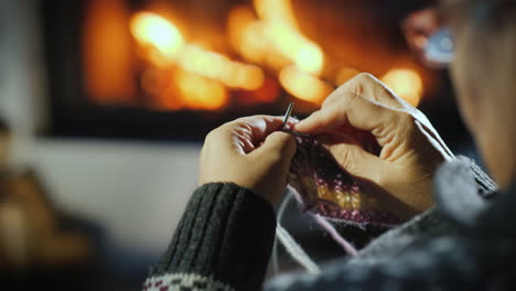 Close-Up-Of-The-Hands-Of-An-Elderly-Woman-Who-Knits-A-Dull-Thing-On-The-Background-Of-The-Fireplace