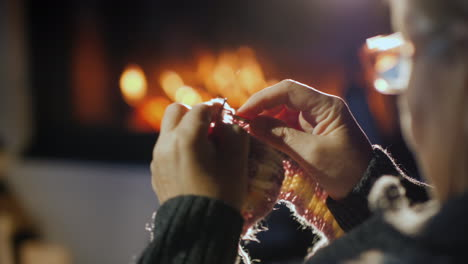 Hands-Of-An-Old-Woman-Knitting-Near-A-Fireplace-In-The-Evening-4k-Video