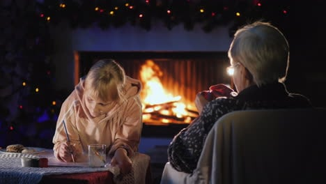 Randmother-With-A-Little-Girl-On-Christmas-Eve-Have-A-Rest-By-The-Fireplace-The-Girl-Writes-A-Letter