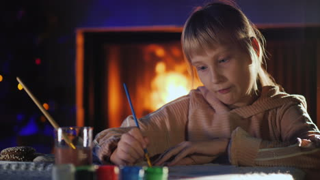 Girl-Paints-Near-The-Fireplace-And-Christmas-Tree