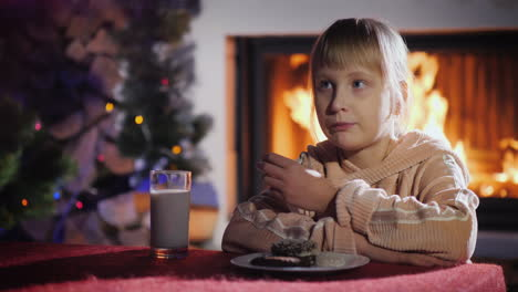 Girl-Eats-Cookies-With-Milk-On-The-Background-Of-The-Fireplace-And-Christmas-Tree
