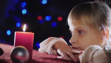 Portrait-Of-A-Child-Looks-At-A-Candle-Makes-A-Wish-On-Christmas-Eve