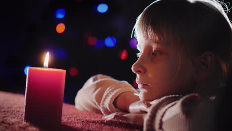 Profile-Portrait-Of-A-Girl-Looks-At-A-Burning-Candle-And-Throws-About-It-On-Christmas-Eve