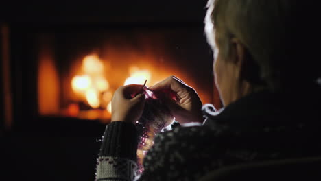 Woman-Handicrafts-By-The-Fireplace-Knits-Warm-Clothes