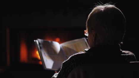 An-Elderly-Woman-In-Glasses-Reads-A-Book-By-The-Fireplace