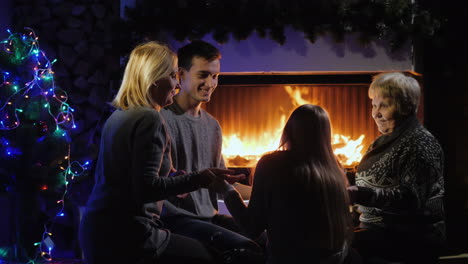 Multi-Generational-Family-Having-Fun-By-The-Fireplace