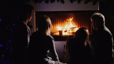 Family-Resting-By-The-Fireplace-Watching-The-Fire-In-The-Dark