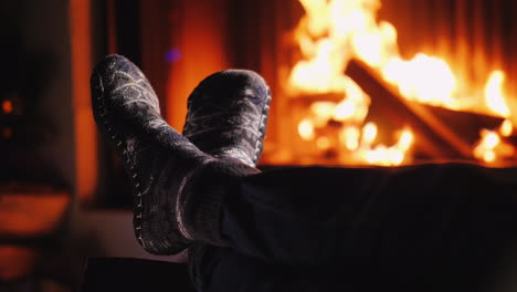 Legs-In-Socks-Near-The-Fireplace-Where-The-Fire-Burns-Evening-By-The-Fire