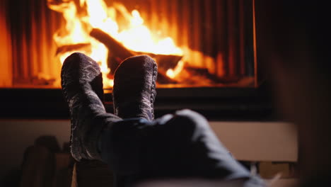 Feet-In-Socks-Against-The-Background-Of-The-Fireplace-Keep-Warm-By-The-Living-Fire