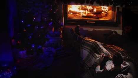 Young-Confident-Man-Resting-By-The-Fireplace-And-Christmas-Tree