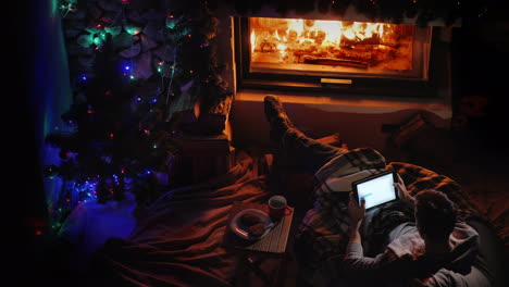Top-View-A-Man-Uses-A-Tablet-By-The-Fireplace-And-Christmas-Tree-Ordering-Holiday-Gifts