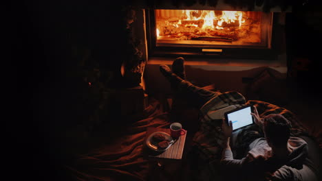 A-Man-With-A-Tablet-In-His-Hands-Has-A-Good-Time-At-Home-By-The-Fireplace