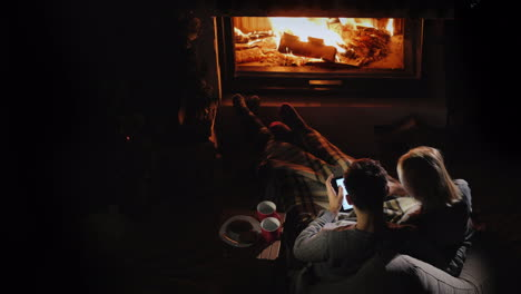 Man-And-Woman-Use-A-Tablet-In-Their-Living-Room-Near-The-Fireplace-Top-View