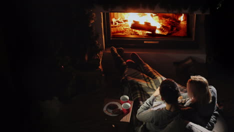Young-Couple-Relaxing-At-Home-By-The-Fireplace-Comfortable-Warm-Home-Concept