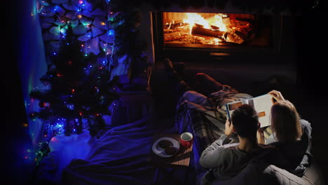 A-Man-And-A-Woman-Read-A-Book-By-The-Fireplace-Where-There-Is-A-Christmas-Tree