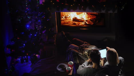 Young-Couple-Admires-The-Fire-In-The-Fireplace-Top-View