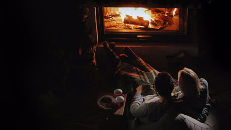 A-Young-Couple-Admires-The-Fire-In-The-Fireplace-Sitting-Next-To-Them-And-Drinking-Tea-Romantic-Dinn