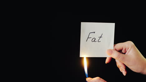 Man-Burns-A-Paper-With-The-Inscription-Fat