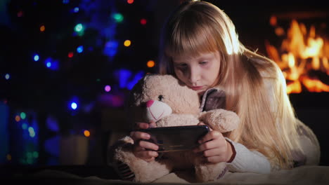 A-Child-With-A-Teddy-Bear-Is-Playing-On-A-Smartphone-Against-The-Background-Of-A-Fireplace-And-A-Chr