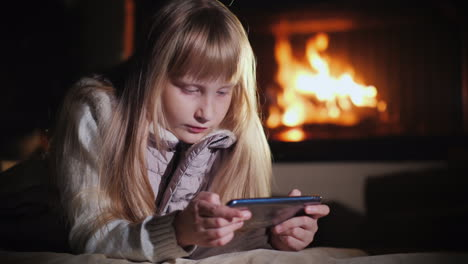 Blonde-Girl-Uses-A-Smartphone-Lies-On-The-Floor-In-The-Room-Against-The-Background-Of-The-Fireplace