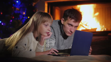 Brother-And-Sister-Use-A-Laptop-In-The-Living-Room-By-The-Fireplace