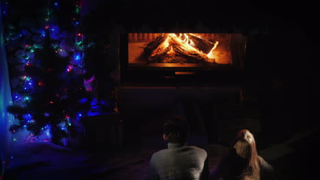 Two-Teenagers-Admire-The-Fire-In-The-Fireplace-Near-The-Christmas-Tree