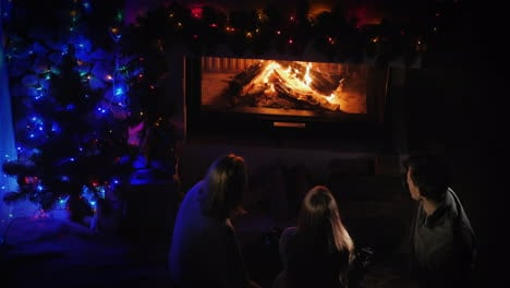 Family-With-Children-Sitting-By-The-Fireplace-And-New-Year-Tree-Top-View