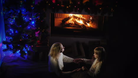 Mom-Plays-With-Her-Daughter-Near-The-Fireplace-And-Christmas-Tree-A-Good-Time-Together