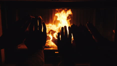 Mom-Dad-And-Baby-Warm-Their-Hands-Together-By-The-Fireplace