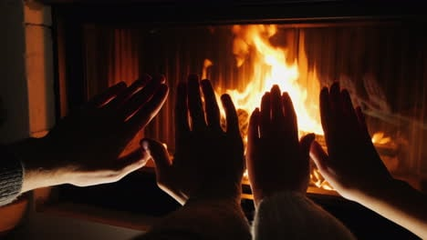 Young-Couple-Warms-Their-Hands-By-The-Fireplace-Romantic-Evening-Together
