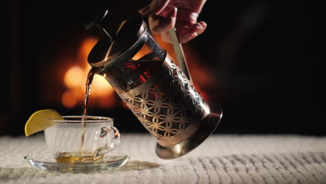 Pour-Tea-Into-A-Cup-On-The-Background-Of-The-Fireplace-Tea-In-A-Cozy-Setting