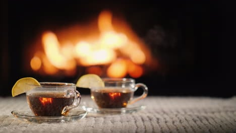 Two-Cups-Of-Hot-Tea-With-Lemon-On-A-Table-Against-The-Background-Of-The-Fireplace