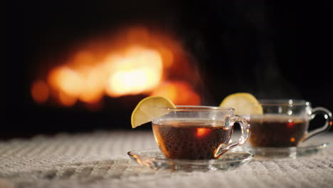 Two-Cups-Of-Hot-Ow-On-A-Table-By-The-Fireplace-Steam-Comes-From-A-Hot-Drink
