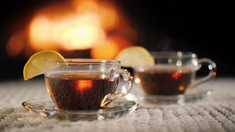 Two-Cups-Of-Tea-With-Lemon-On-The-Background-Of-The-Fireplace-Stand-On-A-White-Knitted-Tablecloth