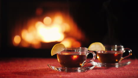 Two-Cups-With-Hot-Tea-On-A-Table-With-A-Red-Tablecloth-In-The-Background-A-Fire-Burns-In-The-Firepla