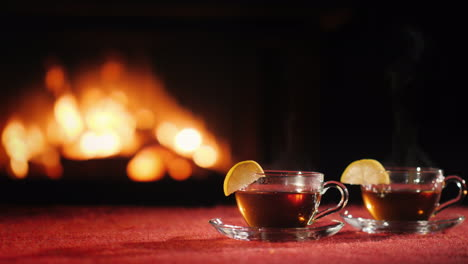 Two-Cups-With-Tea-Stand-On-A-Table-On-A-Black-Background-Where-You-Can-See-The-Fire-In-The-Fireplace