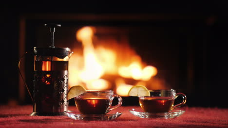 A-Teapot-And-Two-Glass-Cups-With-Tea-Stand-On-A-Table-Against-The-Background-Of-The-Fireplace-Where-