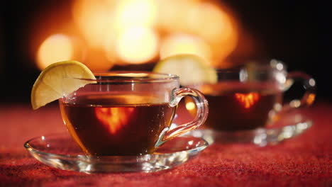Two-Cups-With-Tea-And-Lemon-On-The-Background-Of-The-Fireplace-Where-The-Fire-Burns