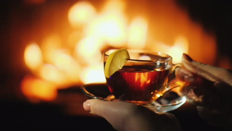 Woman-s-Hands-With-A-Cup-Sat-By-The-Fireplace-Keep-Warm-In-Winter-Concept