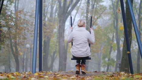 Rear-View-Of-A-Woman-Sitting-On-A-Swing-In-A-Park-Where-There-Is-Heavy-Fog-Loneliness-Concept