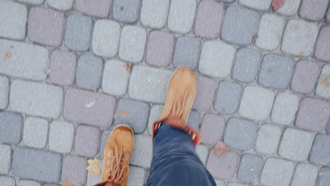 Feet-In-Boots-Walking-On-The-Sidewalk-Paved-With-Tiles