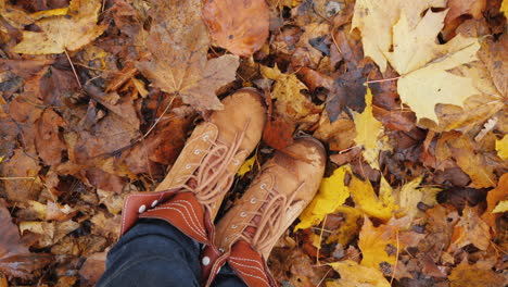Feet-In-Autumn-Boots-On-Fallen-Autumn-Leaves-The-Camera-Rotates