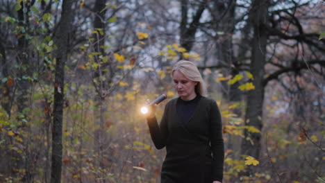 A-Woman-With-A-Flashlight-In-Hand-Walks-Through-The-Woods-At-Dusk