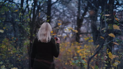 Frightened-Woman-Walks-Through-The-Woods-At-Dusk-Illuminates-Her-Way-With-A-Flashlight