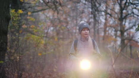 A-Little-Girl-Walks-Through-A-Dark-Forest-With-A-Flashlight-In-Her-Hand-Get-Lost-In-The-Forest-Conce