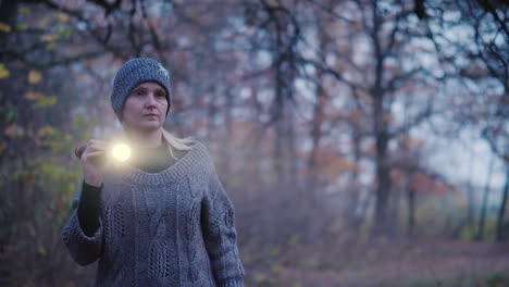 A-Woman-With-A-Flashlight-Is-Walking-Through-A-Dark-Forest-Looking-For-Something-Search-For-The-Miss