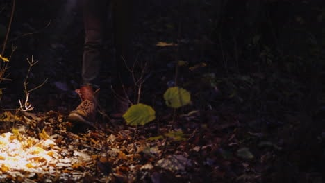Legs-Of-A-Woman-In-Boots-Walking-Along-A-Forest-Trail-Lit-By-The-Light-Of-A-Flashlight