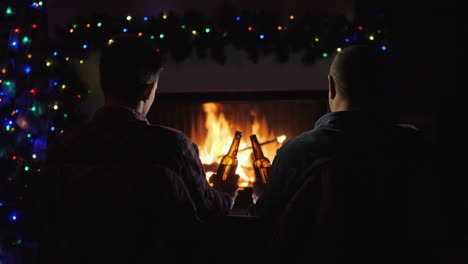 Two-Men-Rest-With-Bottles-Of-Beer-In-Hand-By-The-Fireplace-And-Christmas-Decorations